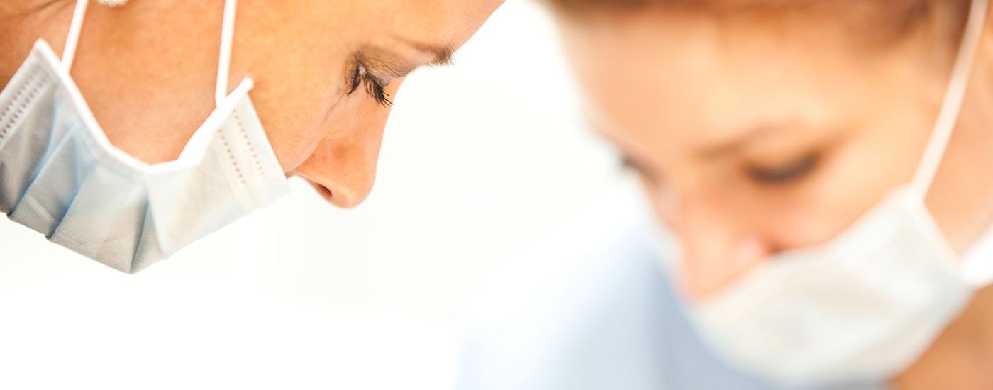 Detailaufnahme: Zahnärztin Heidi Prutean behandelt mit Mundschutz einen Patienten in ihrer Zahnarztpraxis zahn-B in Strausberg.
