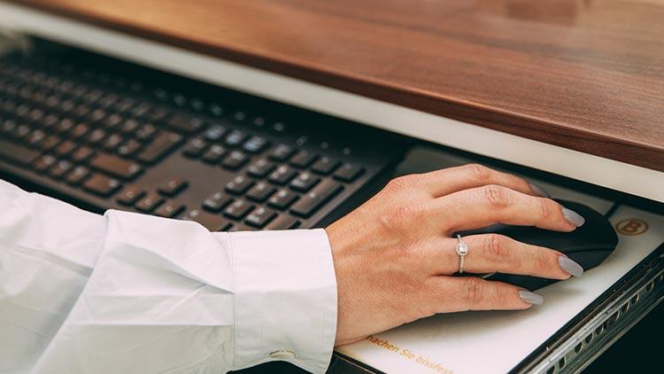 Detailaufnahme: Eine Mitarbeiterin umfasst mit ihrer rechten Hand die Computermaus an der Rezeption.