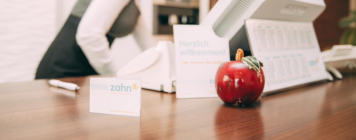Die Rezeption in Großaufnahme: Computer, Kalender, Visitenkarten und ein roter Deko-Apfel begrüßt die Patienten.
