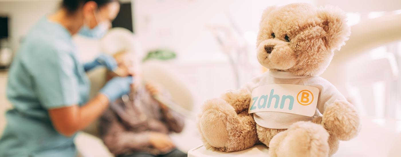 Ein niedlicher Plüschteddy sitzt im Behandlungsraum und beruhigt Angstpatienten bei der Behandlung.