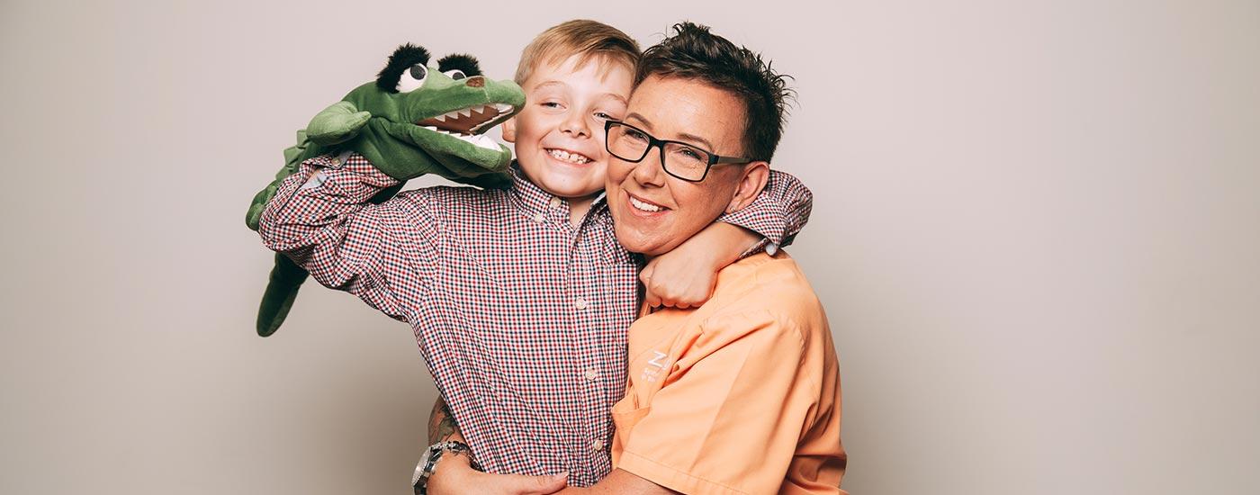 Behandlungsassistentin Ines Graband umarmt einen kleinen Jungen und lebt so das Praxismotto, für die ganze Familie da zu sein.