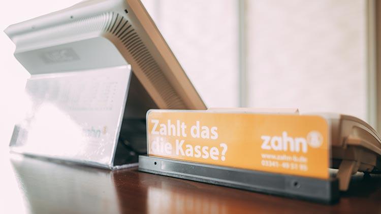 Ein Hinweisschild zum Thema Finanzierung steht an der Rezeption der Praxis zahn-B in Strausberg bereit.