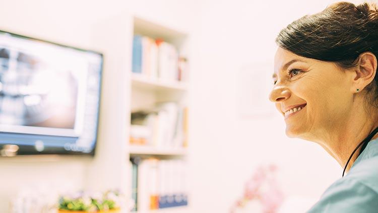 Zahnärztin Heidi Prutean sitzt vor einem Monitor und weiß, dass eine CMD-Therapie Kieferprobleme, Gesichtsschmerzen und Nackenschmerzen verbessert.