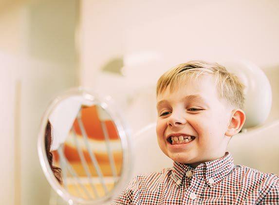 Erfolgreiche Prophylaxe für Kinder: Eine Prophylaxefachkraft zeigt einem kleinen Jungen seine sauberen Zähne im Spiegel.