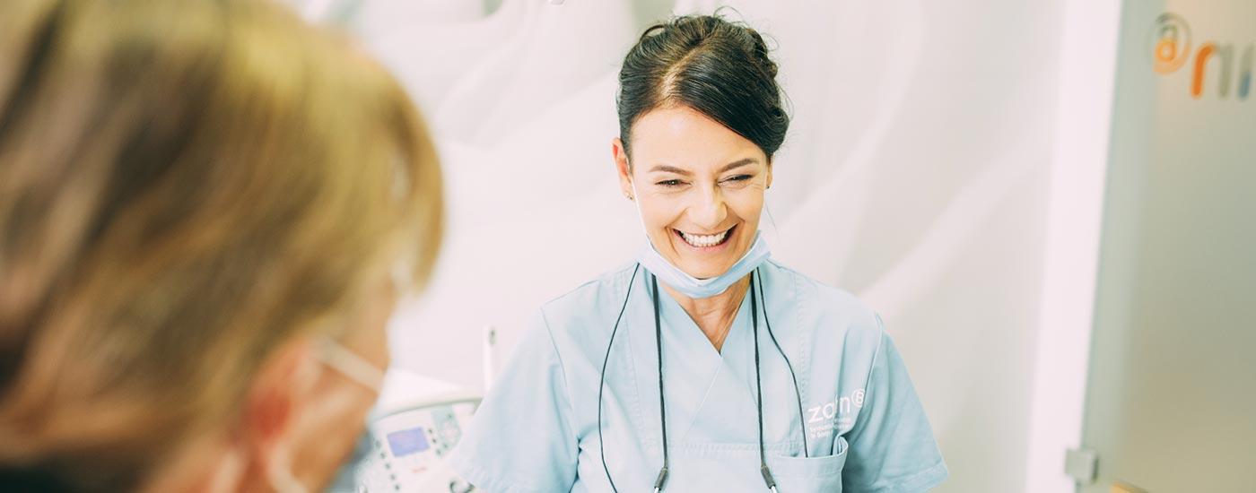 Zahnärztin Heidi Prutean beantwortet einer Patientin lachend deren Fragen rund um die Implantologie.