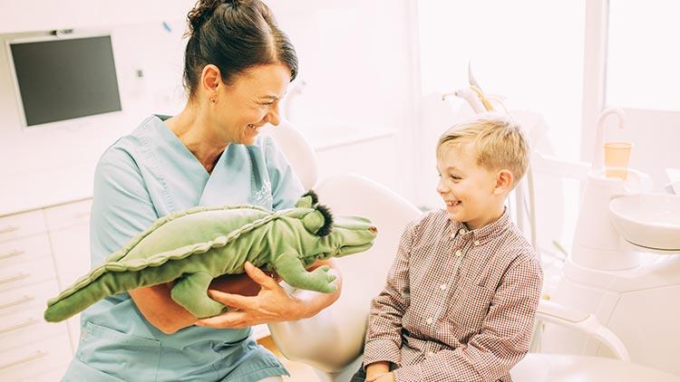 Zahnärztin Heidi Prutean zeigt einem kleinen Patienten mit dem Zahnputzkrokodil, wie wirksame Prophylaxe für Kids funktioniert.