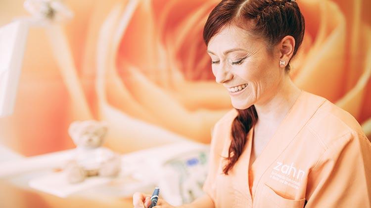 Dentalhygienikerin Katrin Bauer führt lächelnd eine Prophylaxebehandlung durch.
