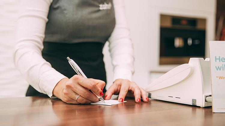 Eine Mitarbeiterin notiert an der Rezeption einen Termin.