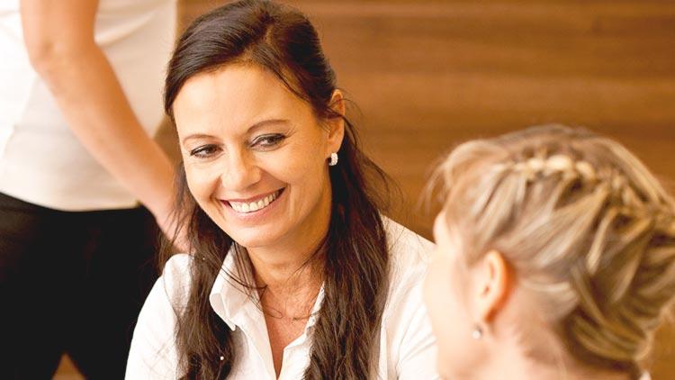 """Dipl. Stom. Heidi Prutean berät eine Patientin freundlich zum Thema """"gesunde Zähne – gesunder Mensch""""."""