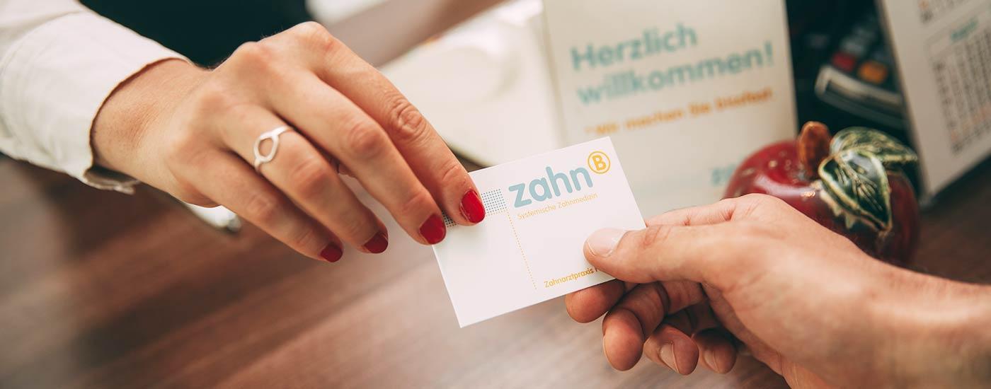 Detailaufnahme zweier Hände: An der Rezeption überreicht eine Praxismitarbeiterin der Patientin eine Visitenkarte mit Kontaktdaten.