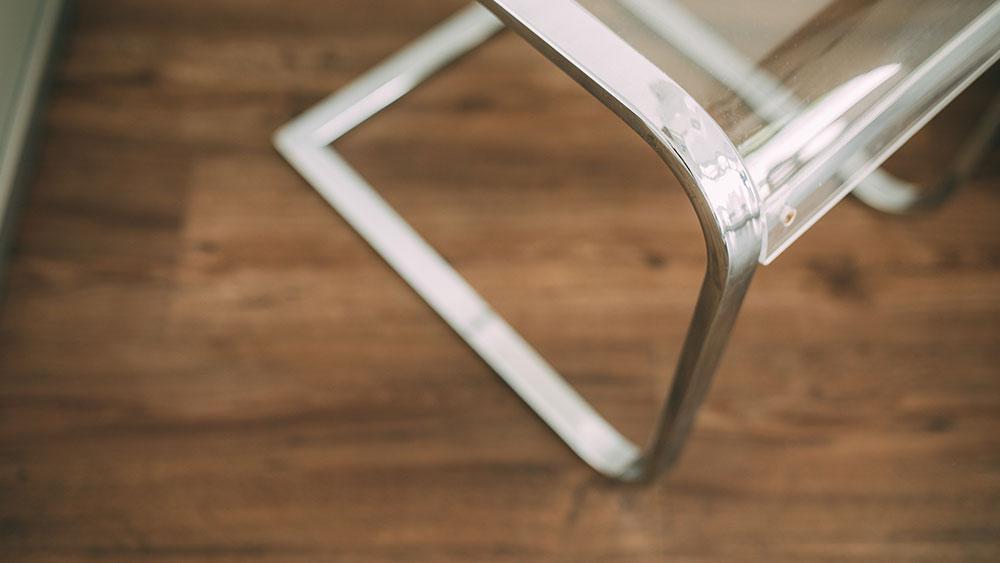 Ein brauner Holzfußboden und ein Stuhl aus Stahl sorgen für einen spannenden Kontrast in der Zahnarztpraxis zahn-B in Strausberg.