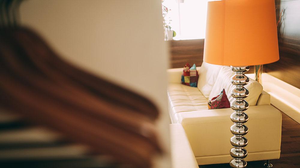 Die moderne Lampe vor dem weißen Sofa im Wartebereich der Zahnarztpraxis zahn-B in Strausberg macht sich gut.