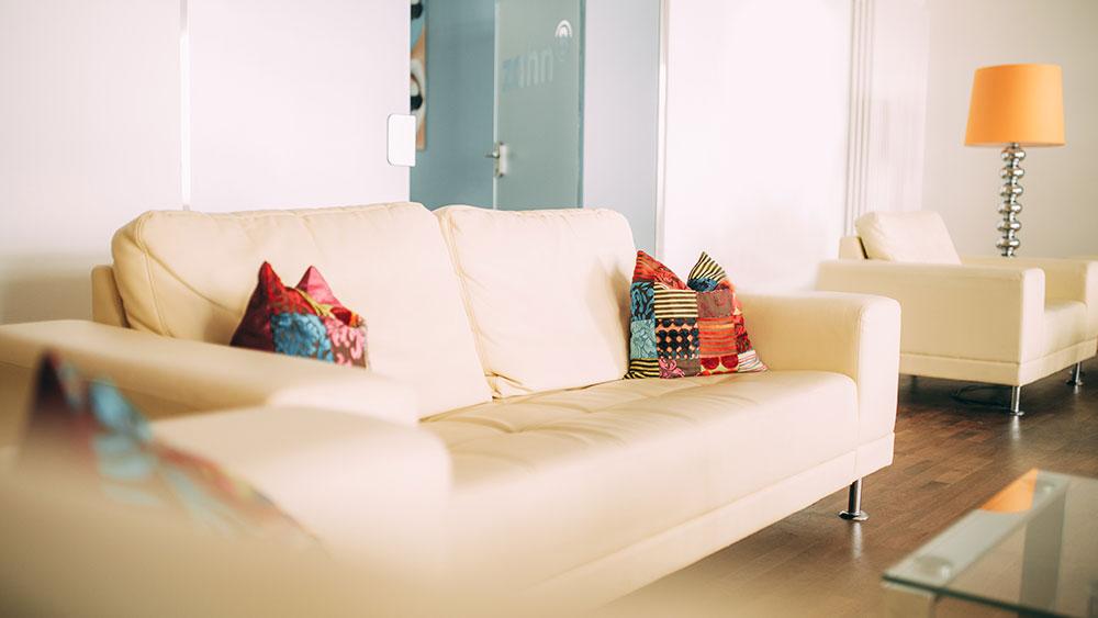 Das weiße Sofa mit bunten Kissen lädt im Wartebereich der Zahnarztpraxis zahn-B in Strausberg zum Verweilen ein.