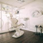 Ein Behandlungszimmer bei zahn-B besticht mit einer wandfüllenden Rosentapete in Weiß.
