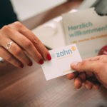 Eine Hand in Großaufnahme überreicht eine Visitenkarte der Zahnarztpraxis zahn-B in Strausberg