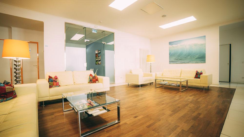 Der großzügige Wartebereich der Zahnarztpraxis zahn-B in Strausberg mit weißen Sofas, Glastisch, braunem Holzfußboden und blauem Bild wirkt sehr einladend.